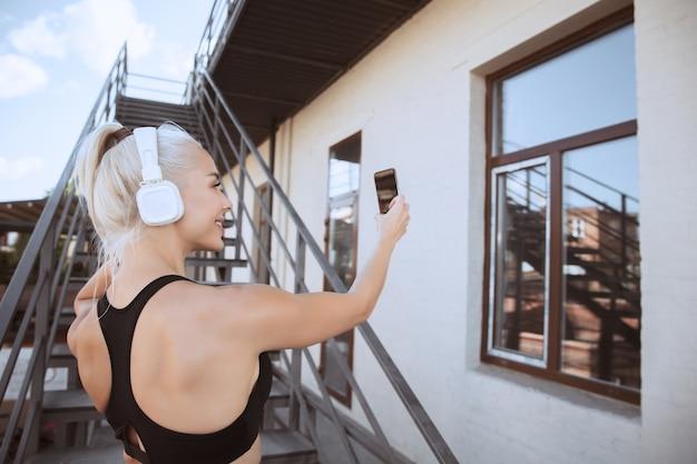 Młoda Kobieta Lekkoatletycznego W Koszuli I Białych Słuchawkach, Pracująca, Słuchanie Muzyki Na Schodach Na Zewnątrz. Robienie Selfie. Pojęcie Zdrowego Stylu życia, Sportu, Aktywności, Utraty Wagi. Darmowe Zdjęcia