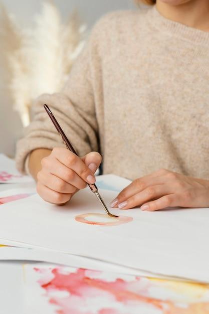 Młoda Kobieta Maluje Akwarelami Na Papierze Premium Zdjęcia