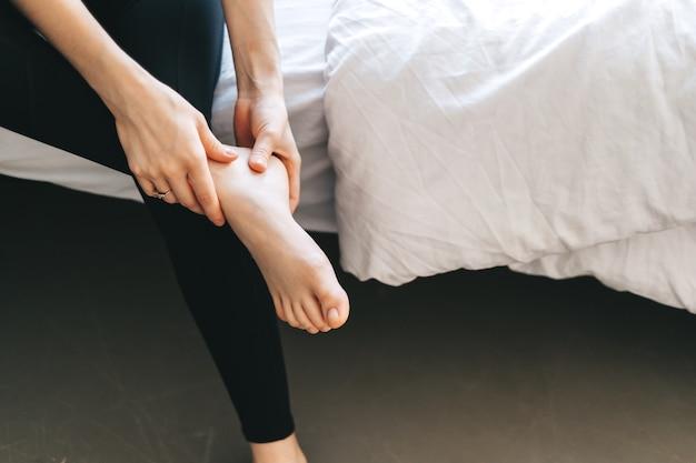 Młoda Kobieta Masuje Stopę Na Białym łóżku Po Treningu Lub Ciężkim Dniu Pracy. Premium Zdjęcia