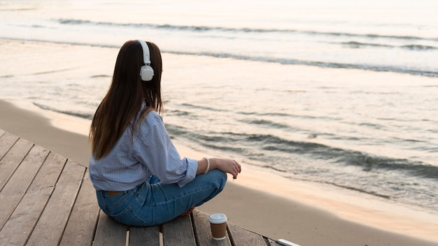 Młoda Kobieta Medytując Nad Morzem, Mając Na Sobie Słuchawki Darmowe Zdjęcia