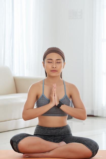 Młoda kobieta medytuje na macie w pokoju Darmowe Zdjęcia