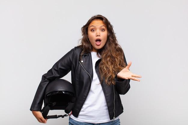 Młoda Kobieta Motocyklistka Czuje Się Wyjątkowo Zszokowana I Zaskoczona, Niespokojna I Spanikowana, Ze Zestresowanym I Przerażonym Spojrzeniem Premium Zdjęcia