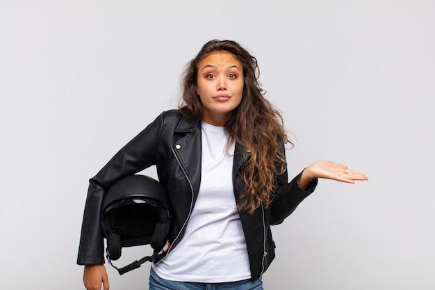 Młoda Kobieta Motocyklistka Czuje Się Zdziwiona I Zdezorientowana, Wątpi, Zważa Lub Wybiera Różne Opcje Z Zabawnym Wyrazem Twarzy Premium Zdjęcia