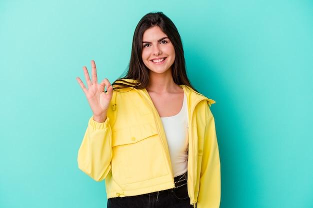 Młoda Kobieta Na Białym Tle Na Niebieskiej ścianie, Wesoły I Pewny Siebie, Pokazując Ok Gest Premium Zdjęcia