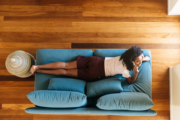 Młoda Kobieta Na Czacie Na Smartfonie Leżąc Na Kanapie W Domu Premium Zdjęcia