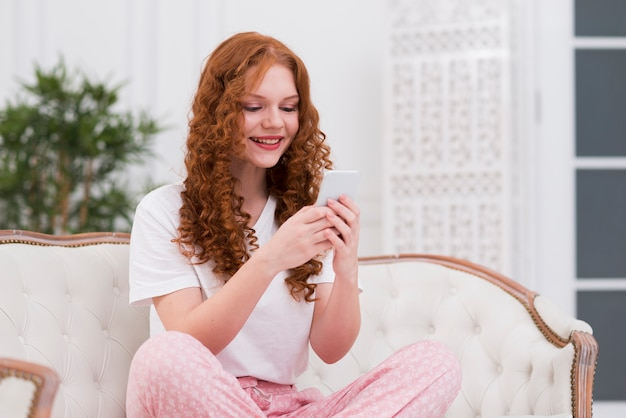Młoda kobieta na kanapie przy użyciu mobile Darmowe Zdjęcia