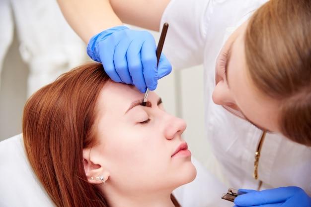 Młoda Kobieta Na Korekcji Brwi W Klinice Kosmetologii. Premium Zdjęcia