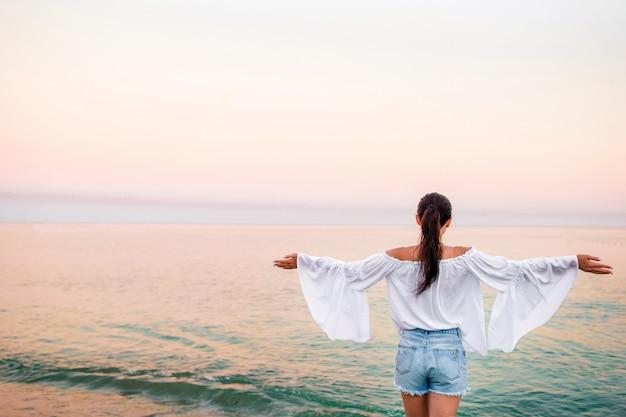 Młoda kobieta na plaży przy zmierzchem Premium Zdjęcia