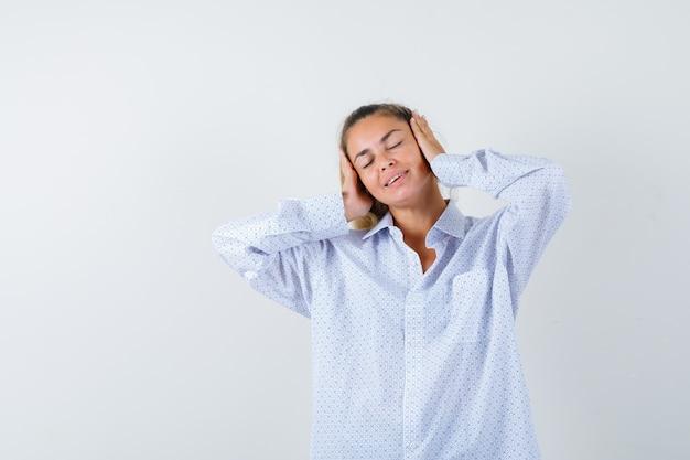 Młoda Kobieta, Naciskając Ręce Na Uszach, Trzymając Oczy Zamknięte W Białej Koszuli I Patrząc Na Szczęśliwego Darmowe Zdjęcia