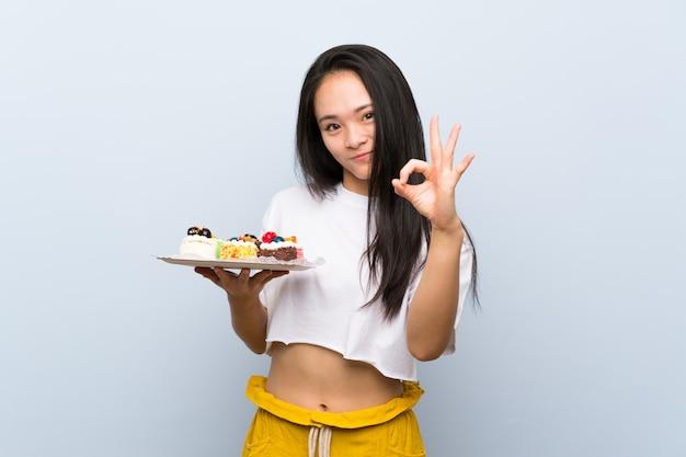Młoda kobieta nad odosobnioną biel ścianą trzyma puchar popcorns Premium Zdjęcia