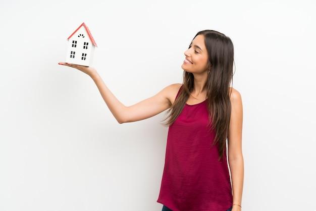 Młoda kobieta nad odosobnioną biel ścianą trzyma troszkę dom Premium Zdjęcia
