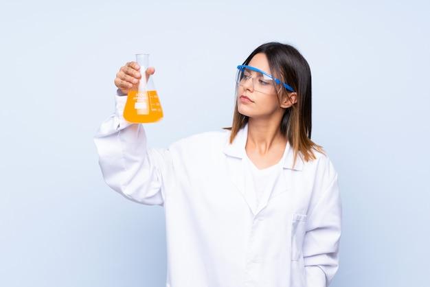 Młoda kobieta nad odosobnioną błękit ścianą z naukową próbną tubką Premium Zdjęcia