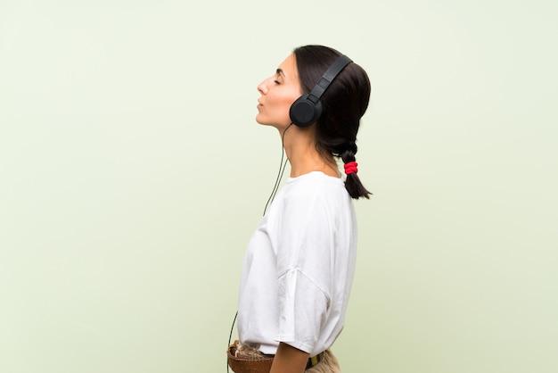 Młoda Kobieta Nad Odosobnioną Zieleni ścianą Słucha Muzyka Z Hełmofonami Premium Zdjęcia