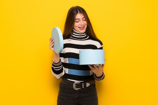 Młoda kobieta nad żółty mur trzymając pudełko w ręce Premium Zdjęcia