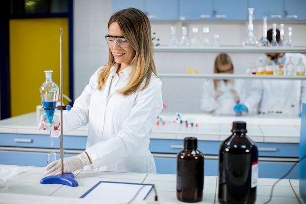 Młoda Kobieta Naukowiec Pracująca Z Niebieskim Płynem W Rozdzielaczu W Laboratorium Premium Zdjęcia
