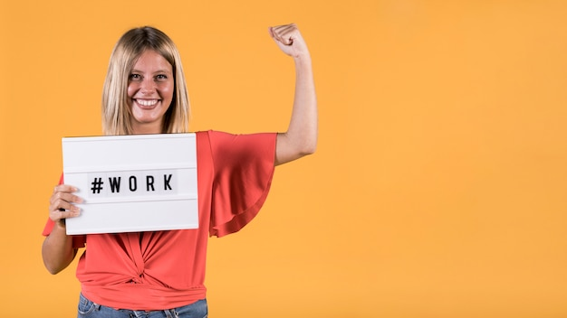 Młoda kobieta niesłysząca gospodarstwa light box z hash tag pracy tekst i wyginanie mięśni na żółtym tle Darmowe Zdjęcia