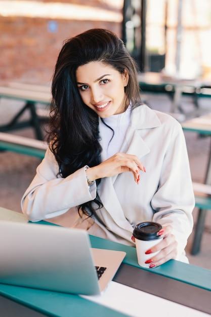 Młoda kobieta o ciemnych włosach, o jasnych oczach, pełnych ustach i zdrowej skórze, ubrana w biały płaszcz odpoczywający w kawiarni i przeglądający internet Premium Zdjęcia