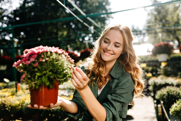 Młoda Kobieta O Pięknych Blond Włosach I Delikatnym Uśmiechu, Ubrana W Zieloną Szatę Z Paskiem, Pracuje W Szklarni Darmowe Zdjęcia