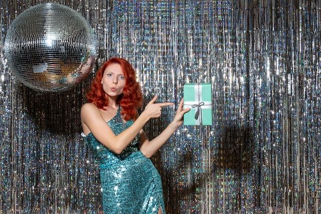 Młoda Kobieta Obchodzi Nowy Rok Trzymając Obecny W Partii Na Jasne Zasłony Darmowe Zdjęcia