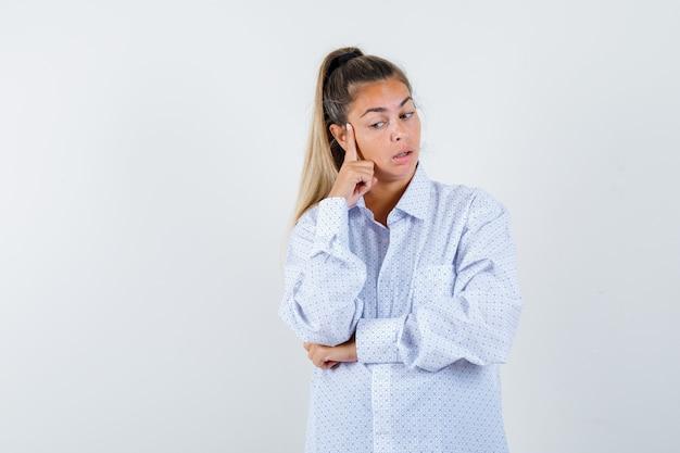 Młoda Kobieta Opierająca Policzek Na Palcu Wskazującym, Myśląca O Czymś W Białej Koszuli I Zamyślona Darmowe Zdjęcia