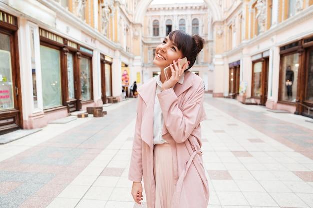 Młoda Kobieta Opowiada Na Telefonie Komórkowym Podczas Gdy Stojący Przy Ulicą Darmowe Zdjęcia