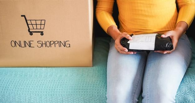 Młoda Kobieta Otwierająca Papierowe Pudełko - Dziewczyna Kupiła Produkty Online Podczas Izolacji Quaratine Premium Zdjęcia