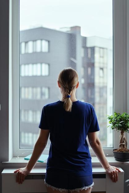 Młoda Kobieta Patrzeje Przez Okno Przy Miastem Darmowe Zdjęcia
