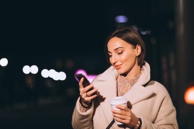 Młoda kobieta pije kawę przy nocy ulicą Darmowe Zdjęcia