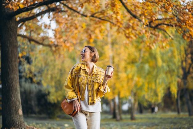 Młoda kobieta pije kawę w jesień parku Darmowe Zdjęcia