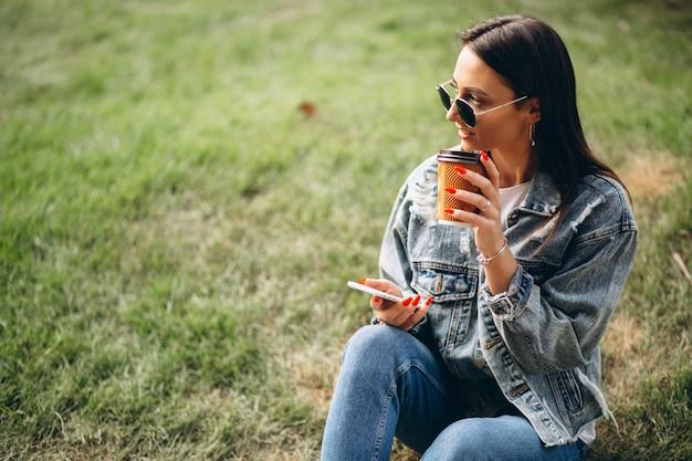 Młoda kobieta pije kawę w parku Darmowe Zdjęcia