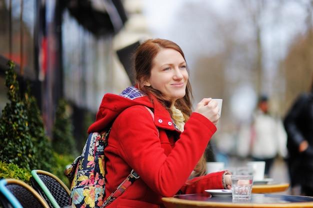 Młoda kobieta pije kawę w paryskiej ulicznej kawiarni przy wiosna dniem Premium Zdjęcia
