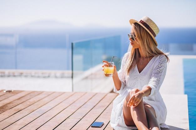 Młoda kobieta pije sok bu basen Darmowe Zdjęcia
