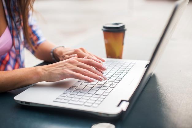 Młoda Kobieta Pisać Na Maszynie Na Laptopie Studiuje Lub Pracuje W Parku Premium Zdjęcia