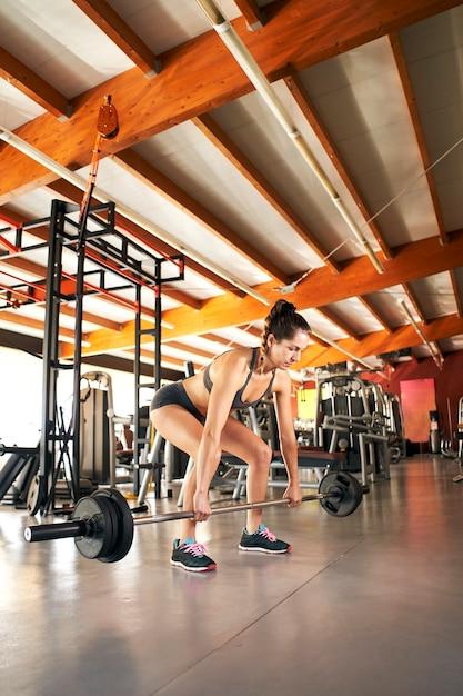 Młoda Kobieta, Podnosząc Sztangę, Patrząc Skoncentrowany, ćwicząc W Samej Siłowni. Premium Zdjęcia