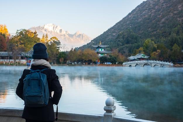 Młoda Kobieta Podróżniczka Podróżująca W Basenie Black Dragon Z Jade Dragon Snow Mountain, Punktem Orientacyjnym I Popularnym Miejscem Atrakcji Turystycznych W Pobliżu Starego Miasta W Lijiang. Lijiang, Yunnan, Chiny Premium Zdjęcia