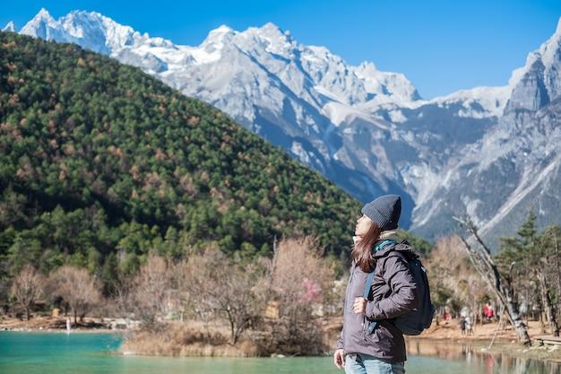 Młoda Kobieta Podróżniczka Podróżująca W Dolinie Blue Moon, Charakterystycznym I Popularnym Miejscu W Jade Dragon Snow Mountain Mountain Scenic Area, W Pobliżu Lijiang Old Town. Lijiang, Yunnan, Chiny. Koncepcja Podróży Solo Premium Zdjęcia
