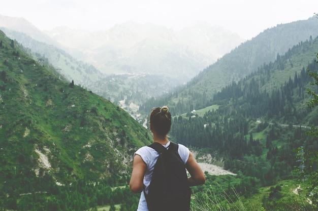 Młoda kobieta podróżnik z plecakiem za plecami Premium Zdjęcia