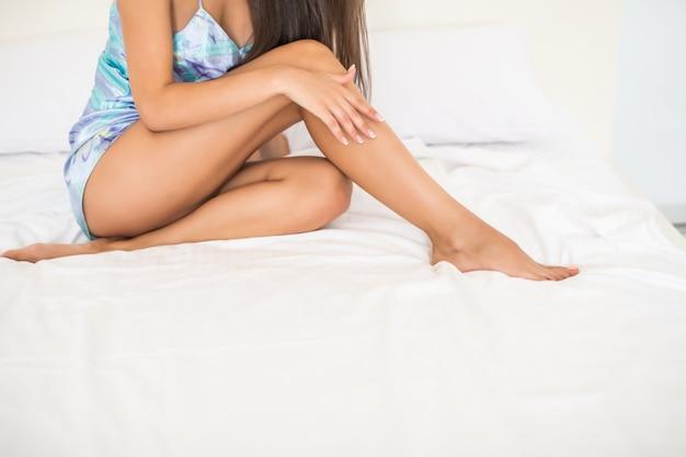 Młoda Kobieta Pokazuje Gładkie Jedwabiste Skóry Nogi Po Depilacji Na łóżku W Domu Darmowe Zdjęcia