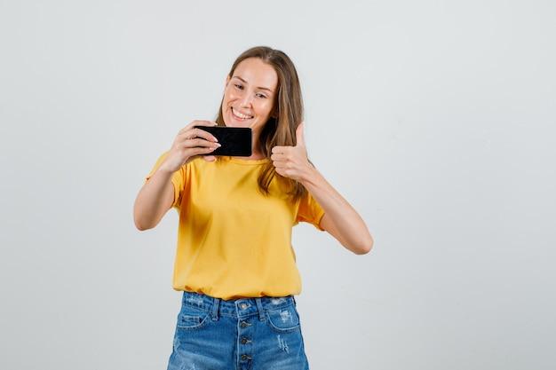 Młoda Kobieta Pokazuje Kciuk W Górę Podczas Robienia Selfie W Koszulce, Spodenkach I Patrząc Zadowolony. Przedni Widok. Darmowe Zdjęcia