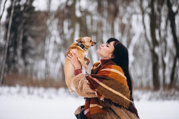 Młoda Kobieta Poza Parkiem Z Jej Małym Psem Przy Zimą Darmowe Zdjęcia