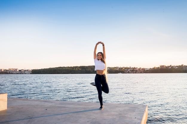 Młoda Kobieta, Pozowanie Na Brzegu Jeziora O Wschodzie Słońca Premium Zdjęcia