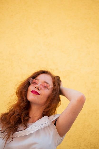 Młoda kobieta pozuje na żółtym tle Darmowe Zdjęcia