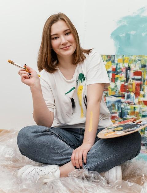 Młoda Kobieta Pozuje Obok Swojego Kolorowego Obrazu Darmowe Zdjęcia