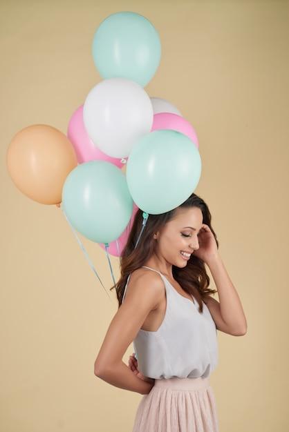 Młoda kobieta pozuje w studiu z wiązką kolorowi helowi balony Darmowe Zdjęcia