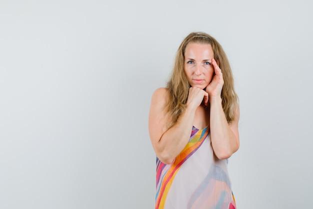 Młoda Kobieta Pozuje Z Brodą Podparty Pięścią W Letniej Sukience I Wygląda Uroczo Darmowe Zdjęcia