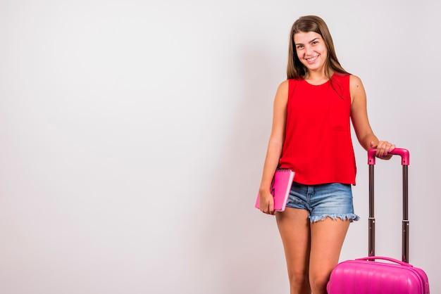 Młoda kobieta pozuje z różową walizką i notatnikiem na białym tle Darmowe Zdjęcia