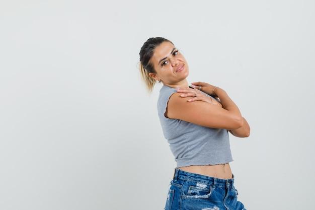 Młoda Kobieta Pozuje Ze Skrzyżowanymi Rękami Na Ramionach W T-shirt, Szorty I ładny Wygląd. Darmowe Zdjęcia