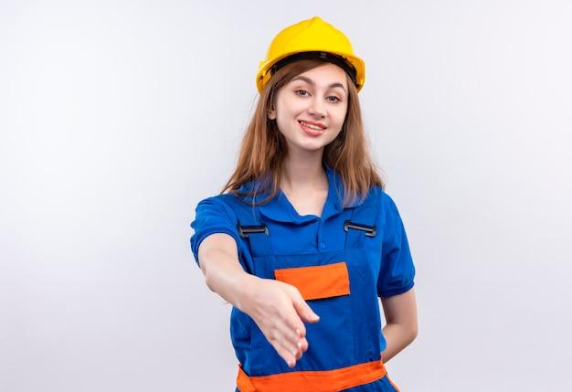 Młoda Kobieta Pracownik Budowniczy W Mundurze Budowlanym I Hełmie Ochronnym Uśmiechnięty Pewnie, że Gest Powitania Oferuje Rękę Stojącą Na Białej ścianie Darmowe Zdjęcia
