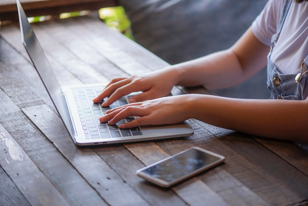 Młoda Kobieta Pracuje Na Laptopie Podczas Gdy Siedzący Na Drewnianej Podłoga Premium Zdjęcia