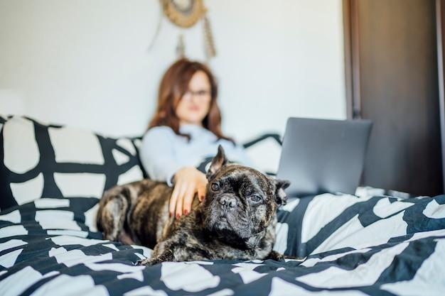 Młoda Kobieta Pracuje Od łóżka W Domu Z Komputerem. Premium Zdjęcia